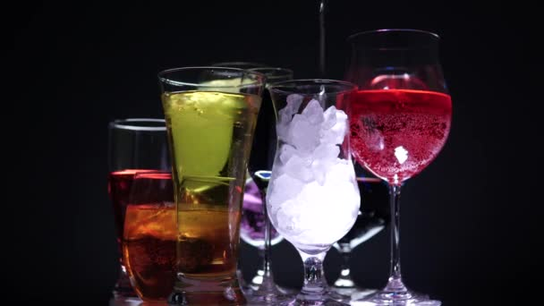 bunte Cocktails in verschieden geformten Gläsern und Eis. Nachtclub Party und Feier Neujahr oder Weihnachten Konzept. Geburtstagsgetränke drehen oder sich auf der Theke drehen.