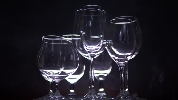 Noční klub pult s různými tvary prázdných sklenic na víno, zpomalené otáčení v baru s mlhou na pozadí. Vánoční nebo novoroční párty koncept nálady. Zavřít.