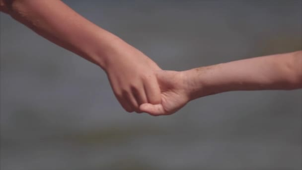 Dvě děti, drželi se za ruce v moři