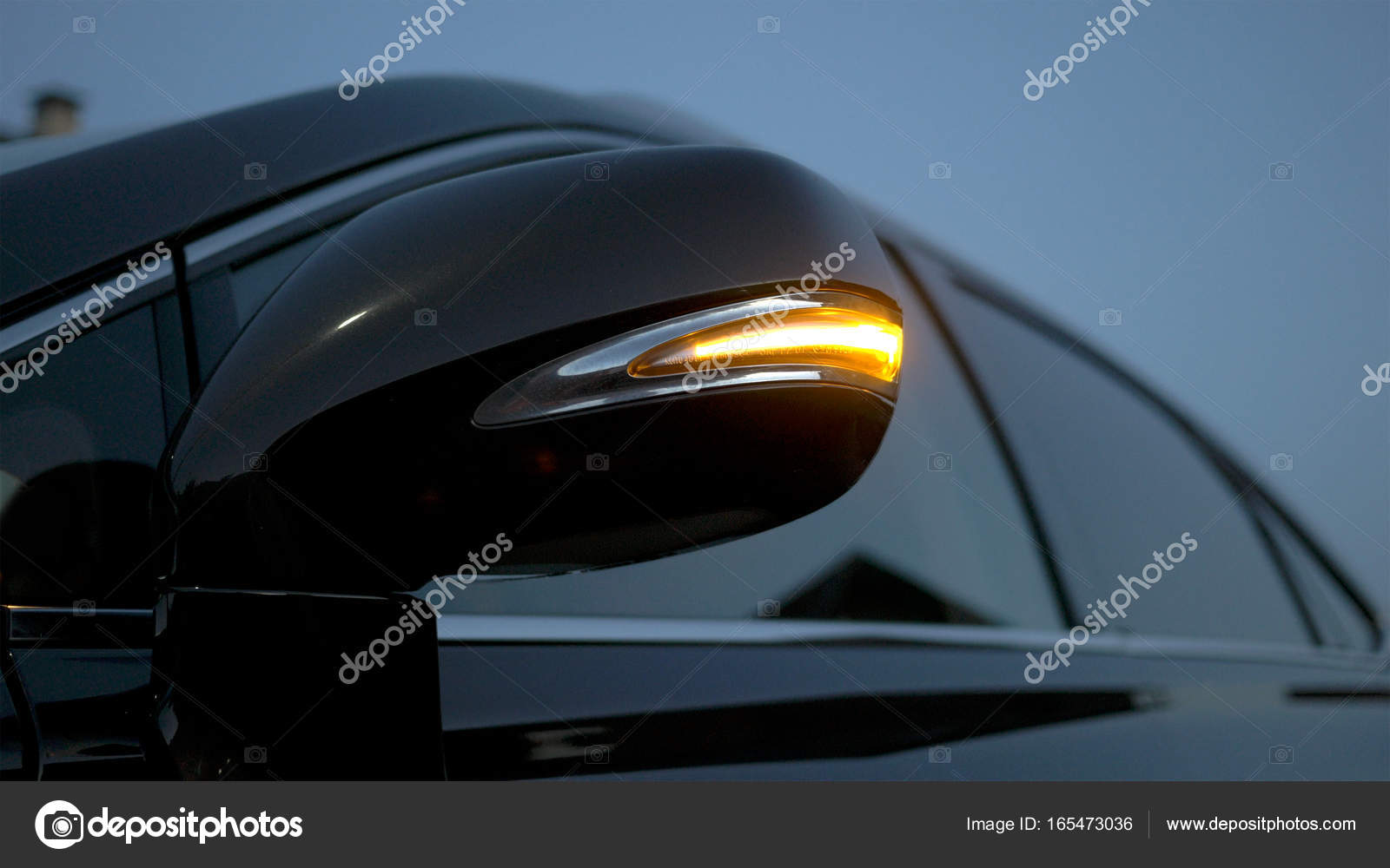 car rear-view mirror. direction indicator is flashing at evening