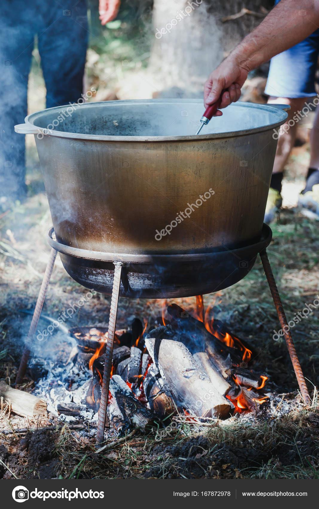 Cocinar en un recipiente de acero inoxidable a fuego ardiente al ...