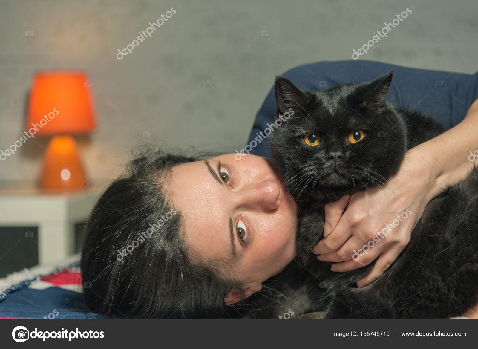 Černá dívka si hraje s kočkou