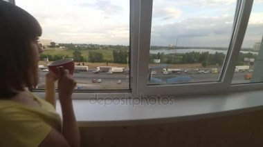 The girl is looking out the window. From the window you can see the motorway
