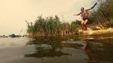 Slow Motion. The guy jumps slowly into the lake