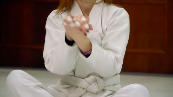 Egy lány a kimonó rakja a judo és a cselgáncs edzés előtt