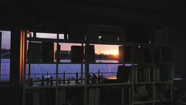 Könyvespolc egy ablakos szobában. Naplemente az ablakban.