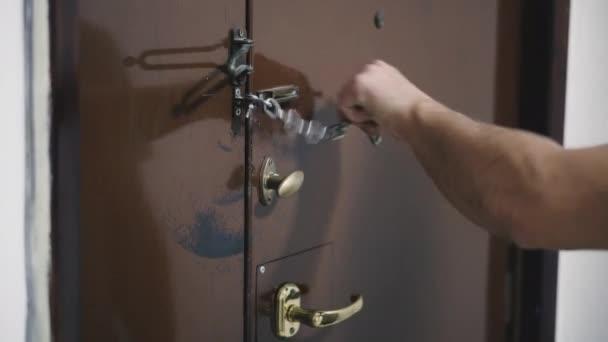 Vstupní dveře. Muž otvírá zámek dveří klíčem..