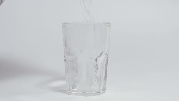 Pití vody. Do sklenice se nalije pitná voda. Natočeno ve zpomaleném filmu.