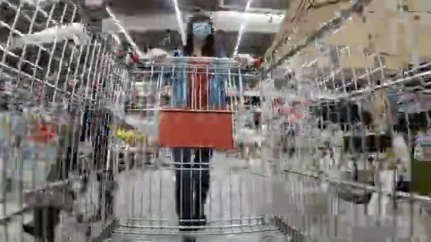 Nákupní košík. Žena v ochranné masce chodí po supermarketu. Převzato v Time Warp.