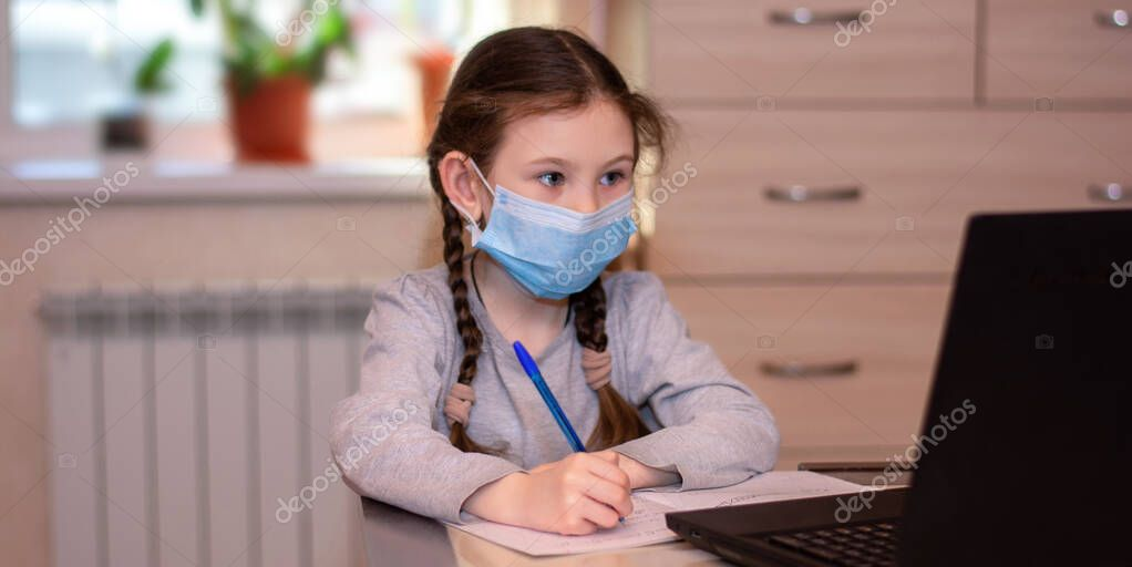 Distance learning online education.School girl in medical mask does homework on laptop at home.Quarantine