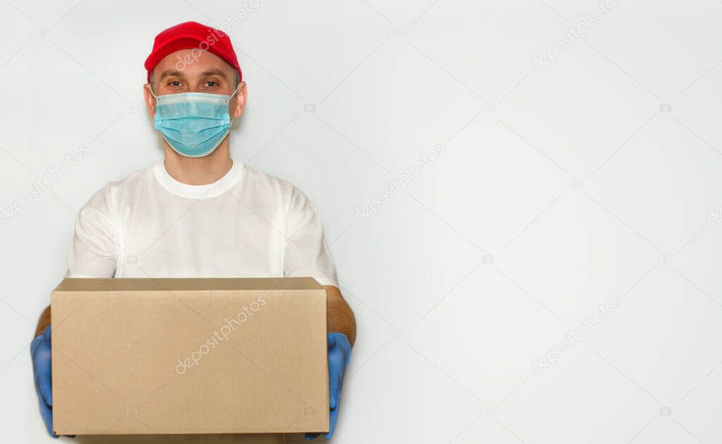 Delivery employee delivering cardboard box in medical gloves and mask.?oncept of safety mail goods courier delivery in virus or coronavirus quarantine. ?opy space on white background