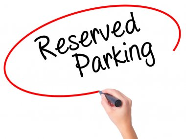 Women Hand writing Reserved Parking with black marker on visual