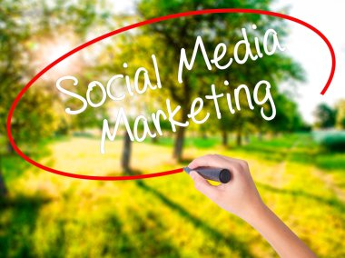 Woman Hand Writing Social Media Marketing with a marker over tra