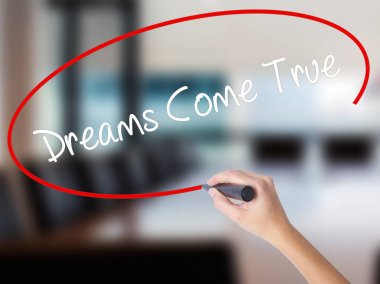 Woman Hand Writing Dreams Come True with a marker over transpare