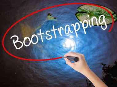 Woman Hand Writing Bootstrapping with marker over transparent bo