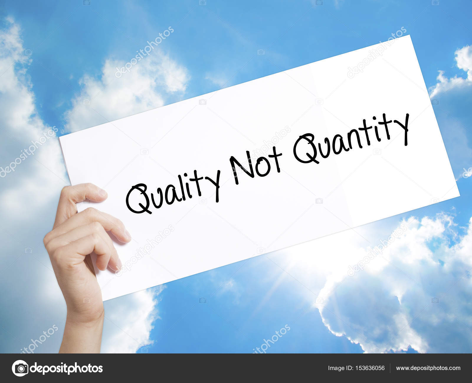quality not quantity sign on white paper man hand holding paper stock photo