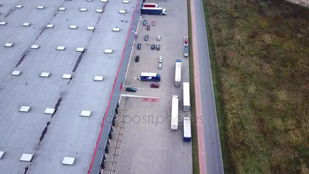 Trucks are Driving to Logistics Center. Aerial Shot./ Storage Building/ Loading Area where Many Trucks Are Loading/ Unloading Merchandise