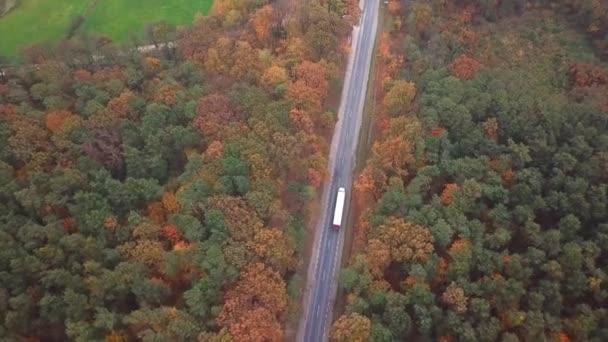 Letěl vysoko nad kontejner semi auto přepravující zboží na dálnici po celé zemi v krásný podzimní večer. Provoz, řízení a zrychlení na rušné dálnici na golden sunset