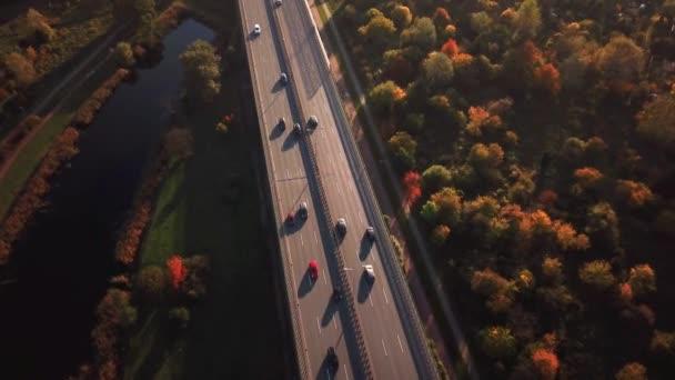 4k letecké: auta a částečně truck jízdy na rušné silnici po celé zemi v krásný podzimní večer. Lidé na výlet cestování na rušné dálnici na golden sunset
