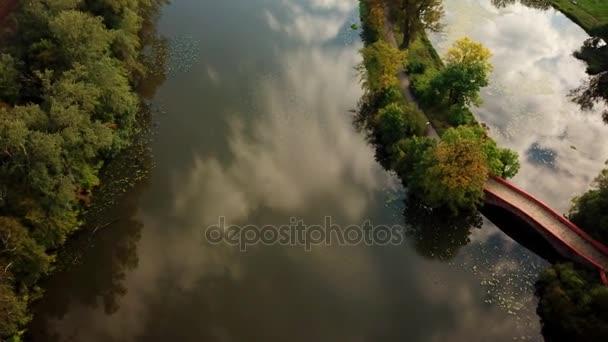 Veřejný park romantické malé pěší most přes rybník se nachází v klidné zelení stromů visí nad obě strany chůze tak krásné místo se přitom mimo vysoké rozlišení 4 k
