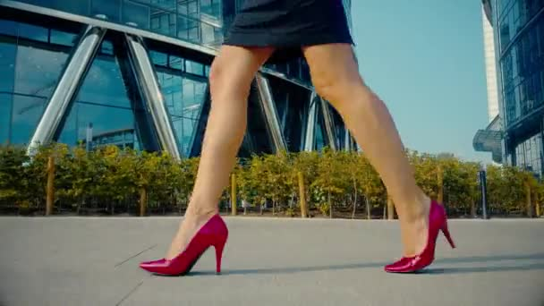 Sexy žena nohy v červené boty na podpatku boty chůze v městské ulici. Steadicam stabilizován zastřelených odlesk objektivu. Ženské nohy v botách na vysokém podpatku v ranní ulice