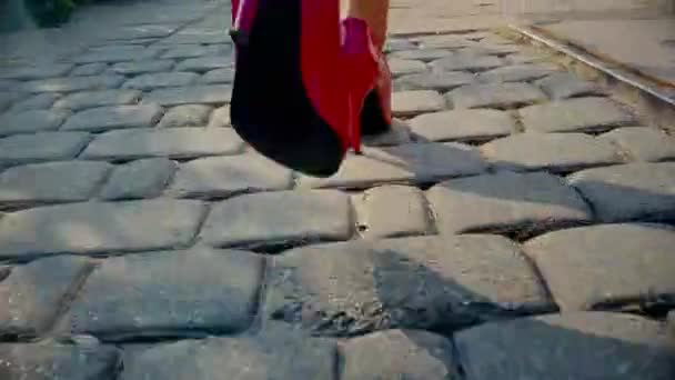 Sexy žena nohy v červené boty na podpatku boty chůze v městské ulici. Steadicam stabilizované zastřelen. Ženské nohy v botách na vysokém podpatku, zblízka. Filmový záběr