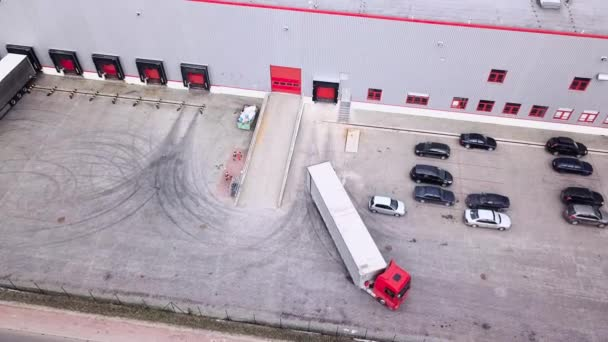 Big distribution warehouse with gates for loads and trucks  Reversing Into A Loading Dock. Aerial Shot