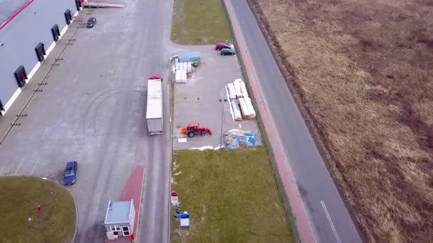 Truck je jízda na logistické centrum. Letecký záběr z průmyslového skladu nakládací rampy kde mnozí náklaďák s Semi přívěsy zatížení zboží