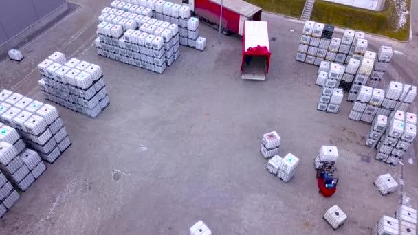 Muž na vozík dopravují náklad z jednoho skladu do auta. Antény. DRONY