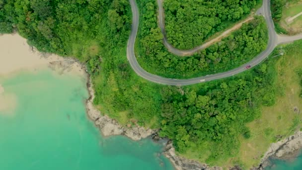 Aerial shot of beauty bay nature landscape with island, cars driving and clear sea with turquoise water on Phuket. Drone