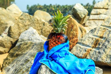 Pineapple in sunglasses on the beach.