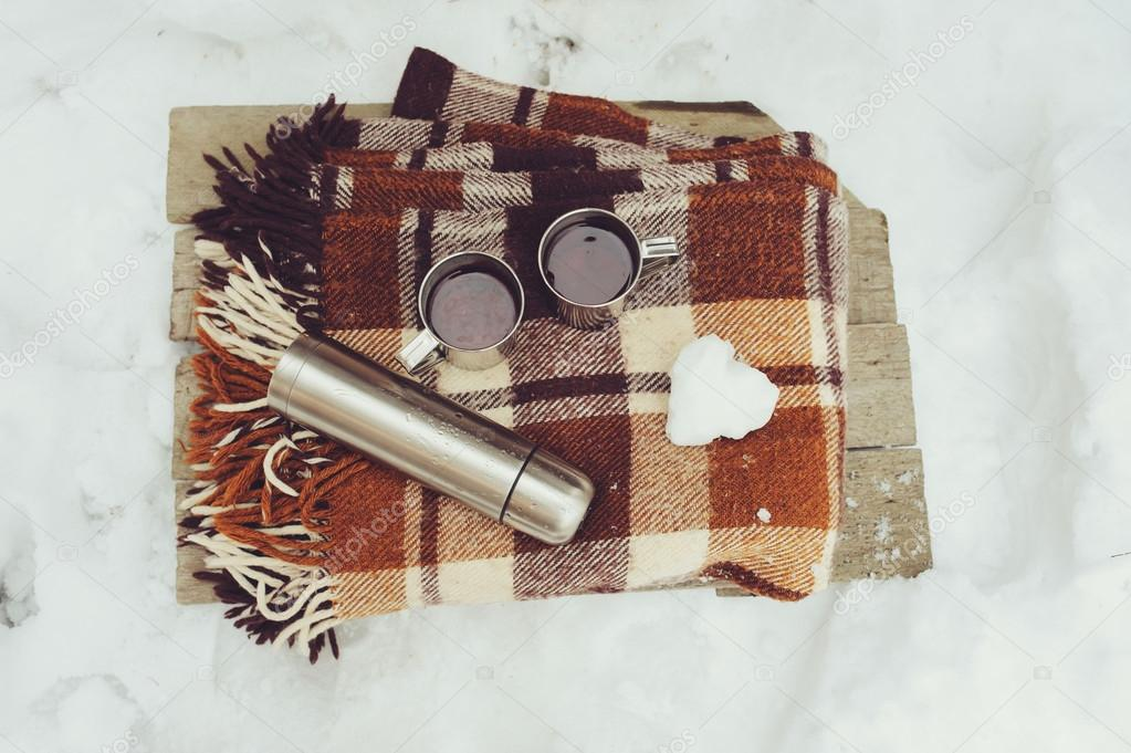 winter picnic on the snow. Hot tea, thermos and snowball heart on cozy warm blanket. Outdoor seasonal activities.