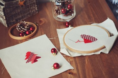 Christmas cross stitch designs and decorations on wooden table. Preparing handmade gifts for New Year and Christmas at home