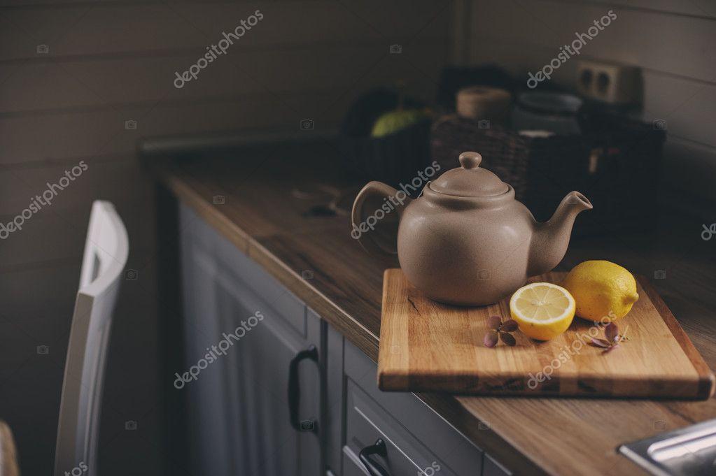 Tetera y limones en el interior de la cocina rústica gris. Lenta ...