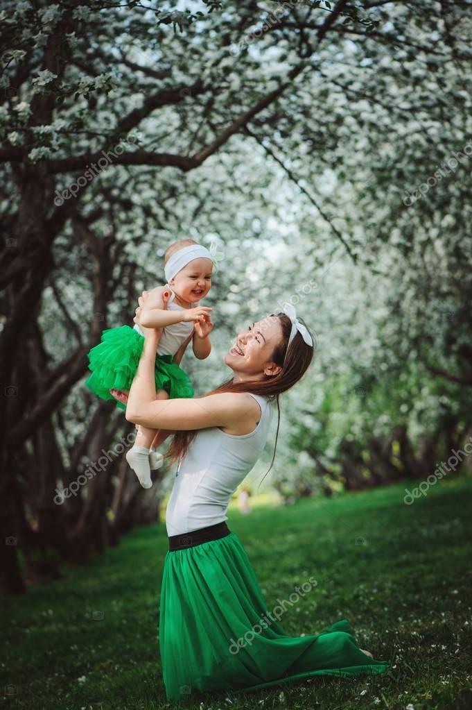 happy mother and baby daughter enjoying walk in spring blooming garden or park