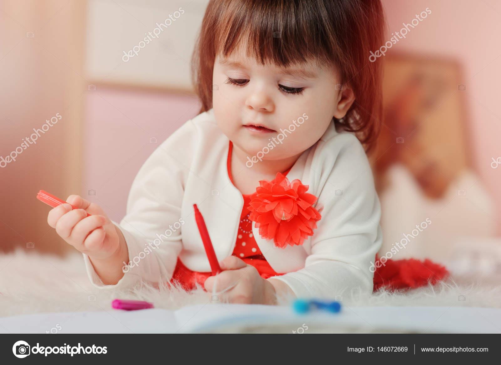 1 Jahr altes Baby Mädchen zeichnen mit Bleistiften zu Hause. Frühe ...