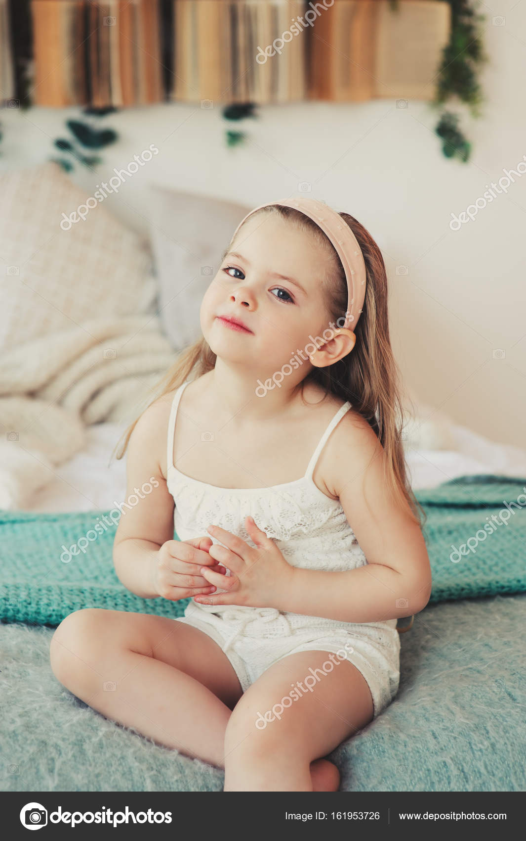 Indoor portrait of sad 5 years old child girl sitting on for 5 yr old beds