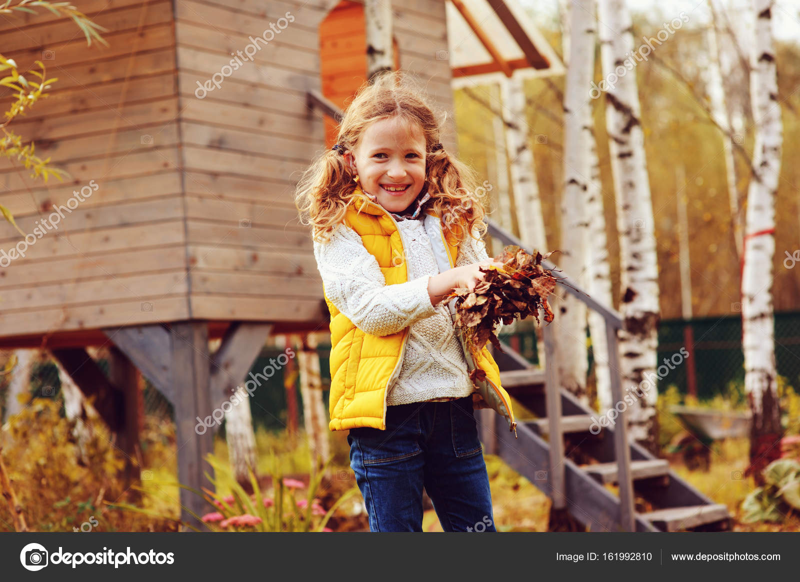 happy child girl playing little gardener in autumn and picking ...