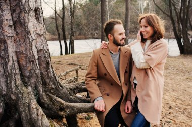 Young happy loving couple walking outdoor in autumn or early spring