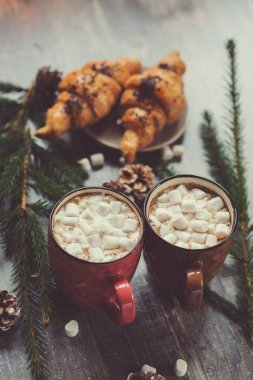 hot cocoa with marshmallows and croissant on rustic wooden table with christmas lights. Cozy winter home concept