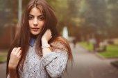 Fényképek portré fiatal szép boldog lány jól kondicionált hosszú, Sötét haja, séta az őszi város meleg kötött pulóvert közelről