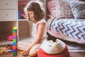 Kind Mädchen reinigen ihr Zimmer und organisieren Holzspielzeug in gestrickten Aufbewahrungstasche. Hausarbeit und Hilfe-Konzept