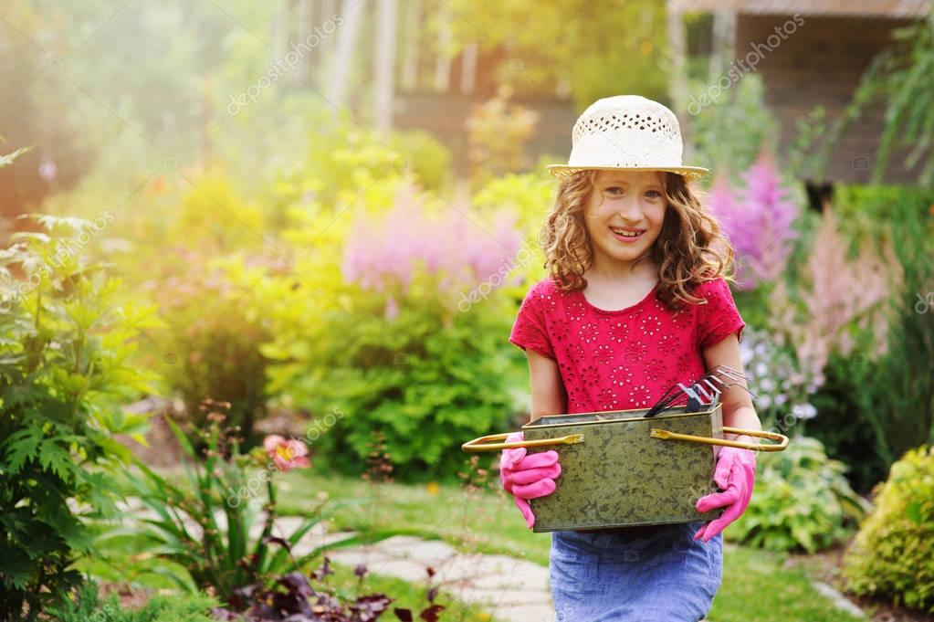 child girl playing little gardener and helping in summer garden, wearing hat and gloves, working with tools