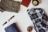summer or autumn woman casual fashion set flat lay with copy space. Plaid shirt, blue cross body bag  and khaki pants on white background. Stylish outfit top view.