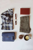 summer or autumn woman casual fashion set flat lay. Plaid shirt, blue cross body bag  and khaki pants on white background with cup of tea. Stylish outfit top view.