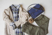 autumn woman casual fashion set flat lay. Plaid shirt, knitted sweater, blue cross body bag  and khaki pants on white background. Stylish outfit top view.