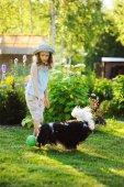 Fotografia ragazza felice del bambino che gioca con il suo cane spaniel e gettando la palla, godendo la giornata estiva di sole nel giardino