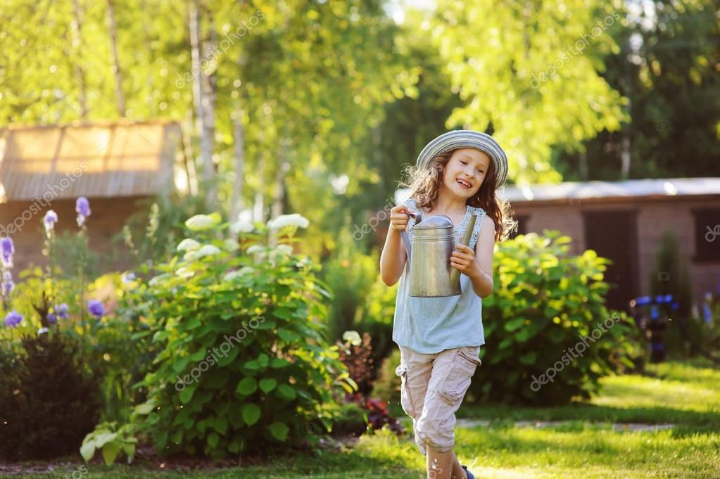 happy funny child girl in gardener hat playing with watering can in sunny summer garden