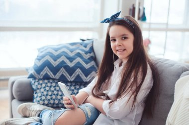 happy preteen girl relaxing at home on cozy couch and listening music, using smartphone