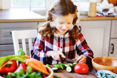 8 years old child girl help mom to cook vegetable salad at home. Healthy eating, little helper concept